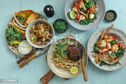 Chicken in a Parmesan and Breadcrumb Crust  served with Crispy Potatoes and Rocket. Beer-braised Beef Cheek with Pearl Barley Risotto. Roasted Pear and Parma Ham Salad with Goats Cheese and Almond Flakes. Salad with Roasted Prawn. Flat lay top-down composition on blue background.