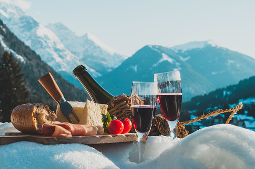 Traditional Italian food and drink outdoor in sunny winter day. Romantic alpine picnic in Dolomites with mountains background, Lambrusco cheese baguette and ham on the snow.