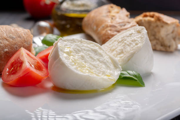 traditional italian food - white ball mozzarella buffalo italian soft cheese with cheese knife, tomato, basil, olive oil - mozzarella foto e immagini stock