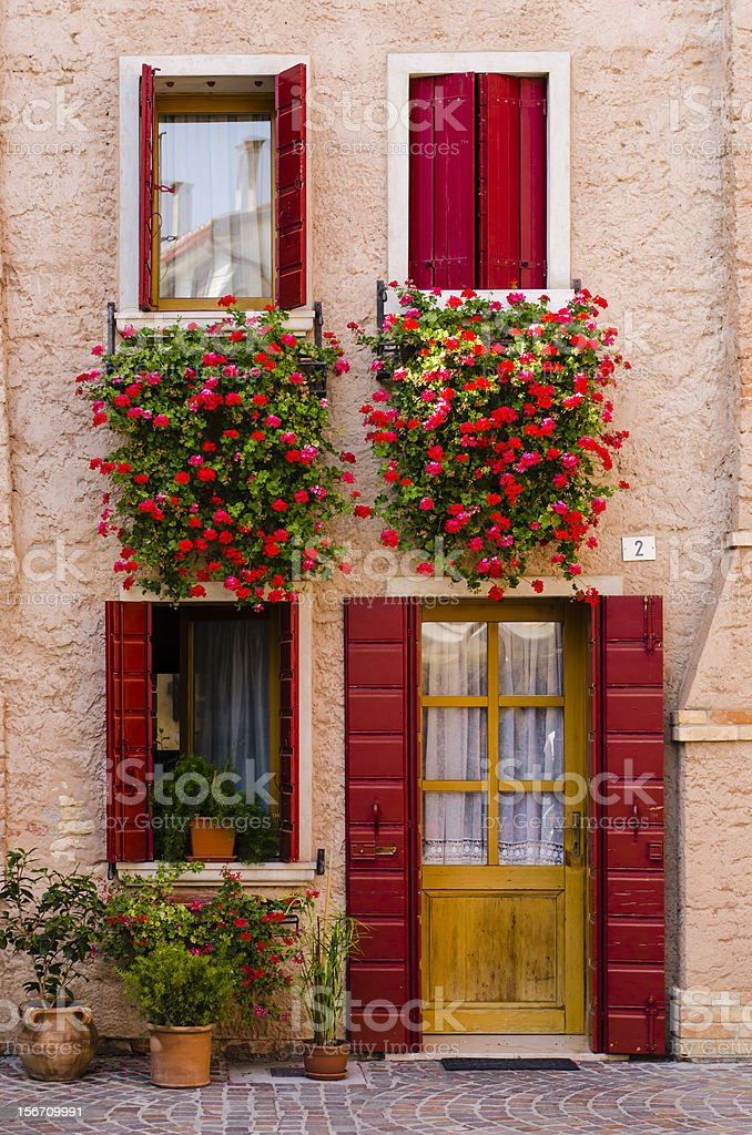 traditional italian house with red windows and geraniums (Caorle, Italy) royalty-free stock photo