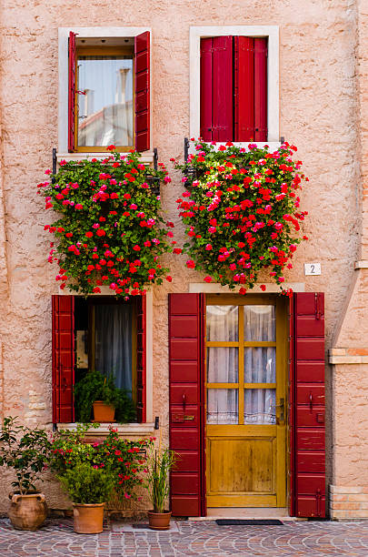 traditional italian house with red windows and geraniums (Caorle, Italy) foto