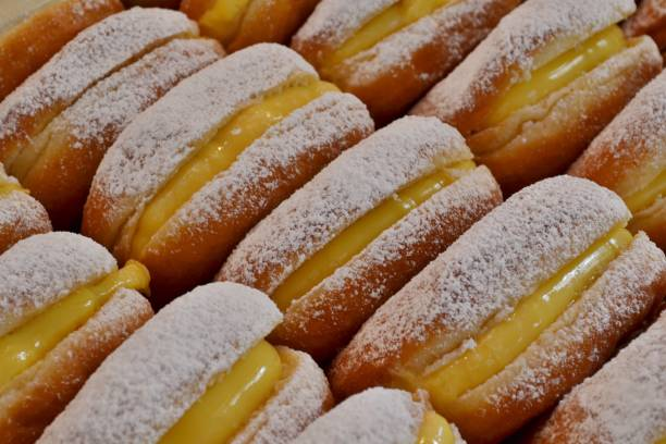 Traditional Italian pastry - krapfen - filled with pasticcera cream - for sale in Christmas kiosks everywhere in Italy. stock photo