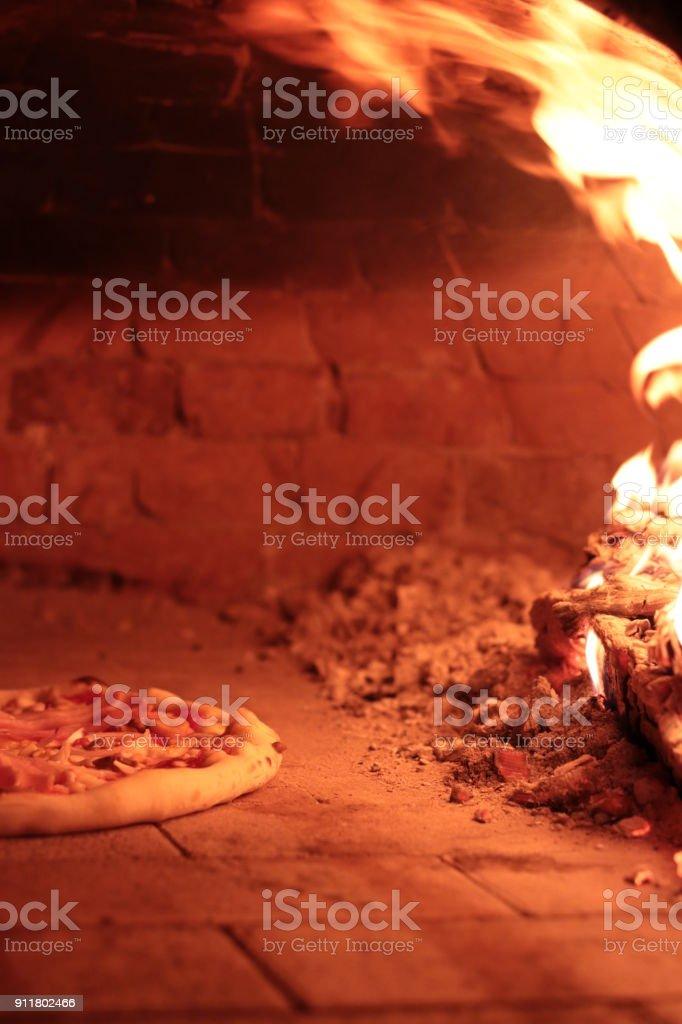 Traditional italian Pizza in Brick oven stock photo