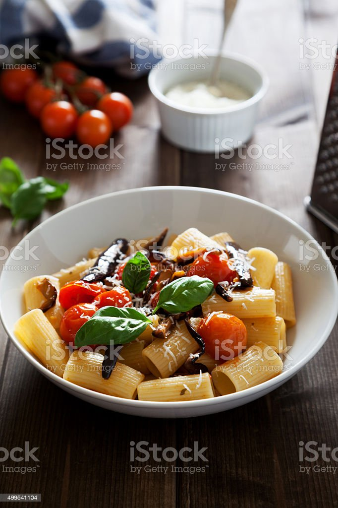 traditional Italian recipe of pasta with eggplant and cherry tomato stock photo