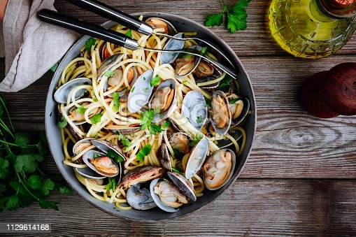 Traditional italian seafood pasta with clams Spaghetti alle Vongole in the pan on wooden background