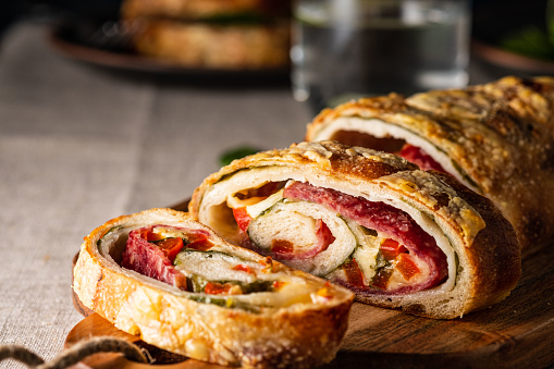 Traditional Italian Stromboli stuffed with cheese, salami, red pepper and spinach. Photo in a dark style.