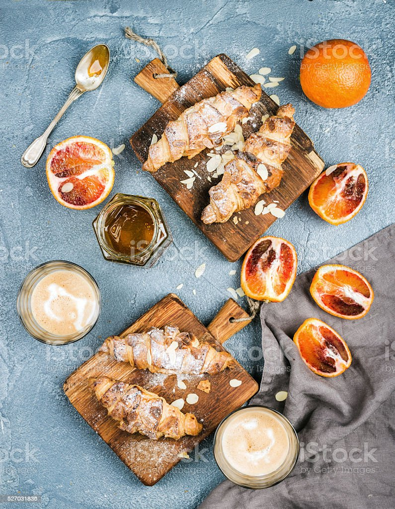 Traditional Italian style home breakfast. Latte in glasses, almond croissants stock photo