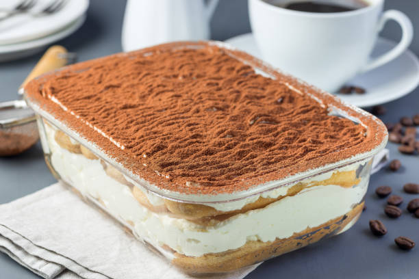 Traditional italian Tiramisu dessert cake in a glass form, decorated with cocoa powder with coffee cup, on gray background, horizontal Traditional italian Tiramisu dessert cake in a glass form, decorated with cocoa powder with coffee cup, on a gray background, horizontal tiramisu stock pictures, royalty-free photos & images