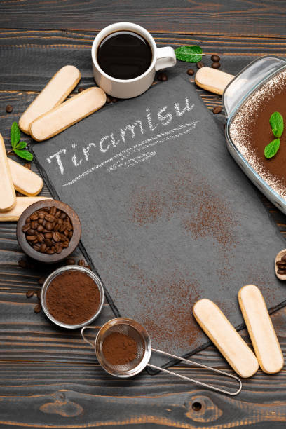 Traditional Italian Tiramisu dessert in glass baking dish, cup of coffee and savoiardi cookies on stone serving board with chalk inscription sign on wooden background stock photo