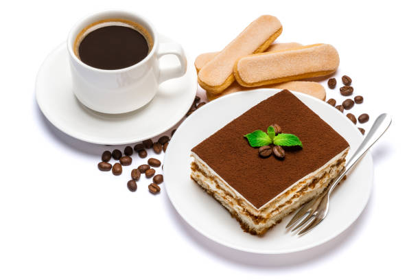 Traditional Italian Tiramisu dessert square portion on ceramic plate, savoiardi cookies and cup of fresh espresso coffee isolated on white background with clipping path stock photo