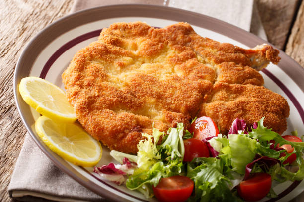 traditional italian veal milanese with lemon and fresh vegetable salad close-up. horizontal - escalope imagens e fotografias de stock