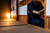 伝統的な日本の家や着物を着た男との旅館畳の上で滑る障子