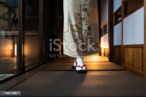 Traditional japanese house or ryokan with tatami mat floor and shoji sliding paper doors and woman in kimono and geta shoes tabi socks walking