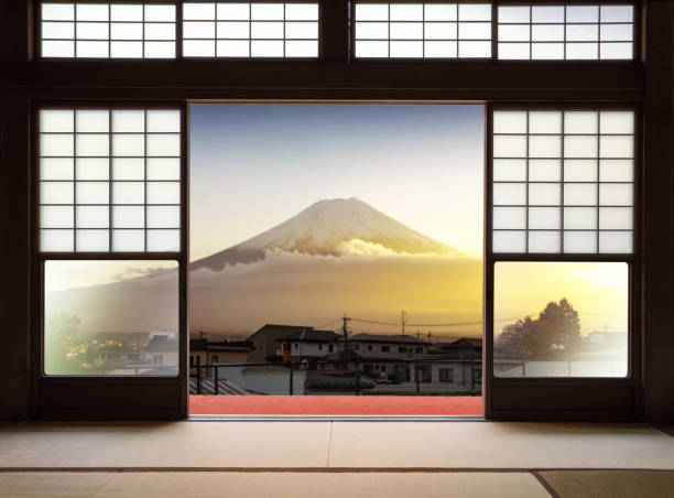 Traditional Japanese indoor  house and paper sliding doors and tatami mat open to View of a beautiful Fuji mountain in sunset and japanese house in autumn season. Kawaguchiko, Yamanashi, Japan stock photo