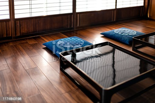 Traditional japanese machiya house or ryokan restaurant with black lacquered wooden table, cushion pillows and sliding paper doors with natural bright light