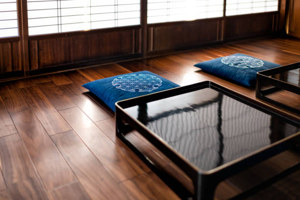 Traditional japanese machiya house or ryokan restaurant with black lacquered wooden table, cushion pillows and sliding paper doors with natural bright light stock photo