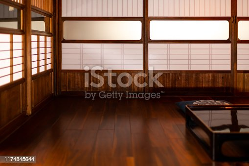 Traditional Japanese machiya house or ryokan restaurant with black lacquered wooden table, cushion pillow and sliding paper doors with natural bright soft light
