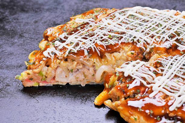 traditional japanese okonomiyaki pancake on hot black pan - teppan yaki grill stock-fotos und bilder