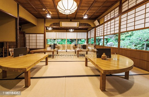 This is a photograph of the interior of a restaurant with wooden tables and floor seating in Kyoto, Japan.