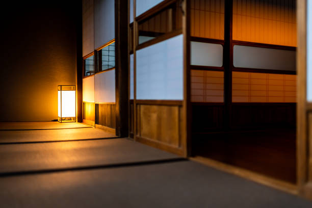 Traditional japanese room low angle view in house or ryokan with open shoji sliding paper doors tatami mat floor and lamp illuminated at night with nobody stock photo