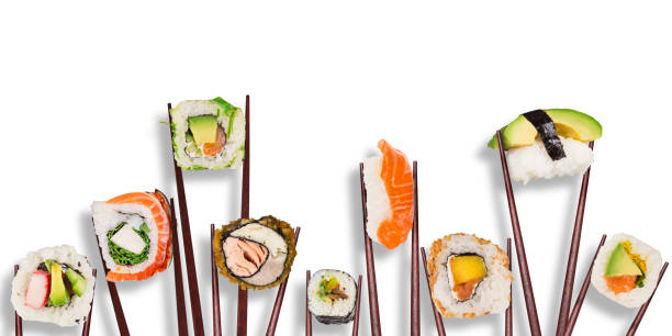 traditional japanese sushi pieces placed between chopsticks, separated on white background - banchi di pesci foto e immagini stock