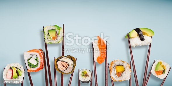 istock Traditional japanese sushi pieces placed between chopsticks, separated on light blue pastel background 958696436