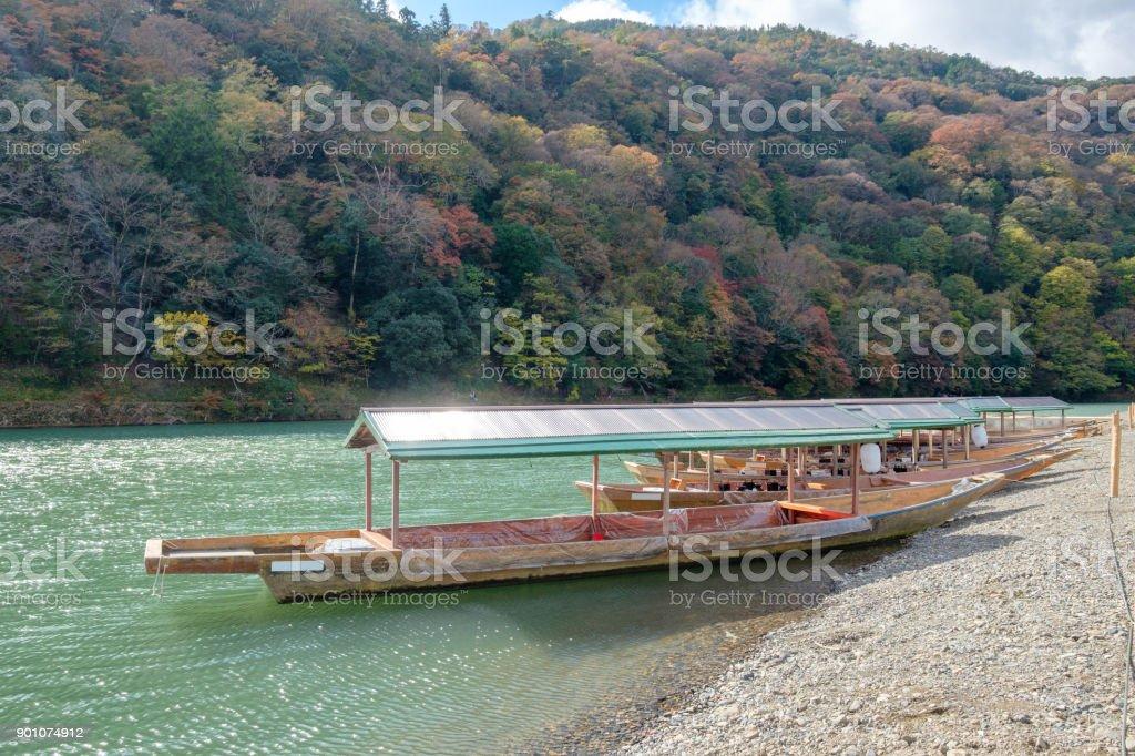 Traditional japanese wooden boat anchored on green river in autumn season at Arashiyama stock photo