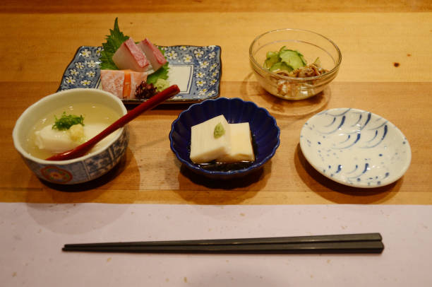 a traditional japenese tofu appetiser, pickled vegetable and sashimi in a kyoto restaurant - appetiser stock photos and pictures