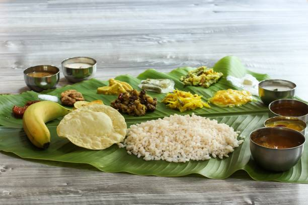 Traditional Kerala Onam Sadya   served in Banana Leaf / Vegetarian meal boiled rice curries and Papad served during festival stock photo