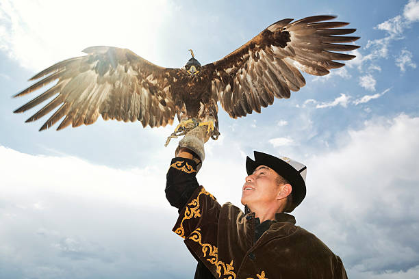 Traditional Kyrgyz Hunter Holding Eagle Hunting with golden eagles is a traditional art of the Eurasian steppes, particularly in Central Asia. kazakhstan stock pictures, royalty-free photos & images