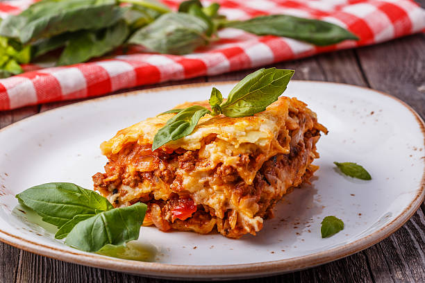 Traditional lasagna made with minced beef bolognese sauce. Traditional lasagna made with minced beef bolognese sauce and bechamel sauce  topped with basil leaves. bolognese sauce stock pictures, royalty-free photos & images