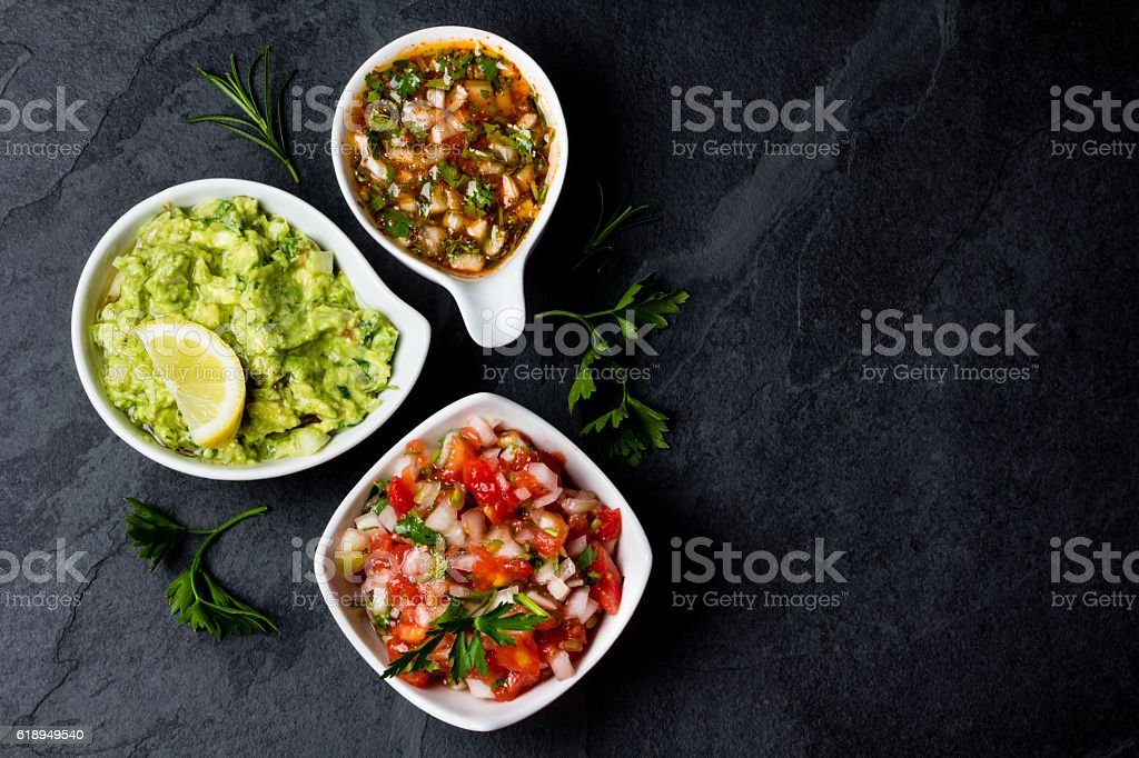 Traditional Latin American sauces Guacamole, Salsa, chili Pebre, slate background stock photo