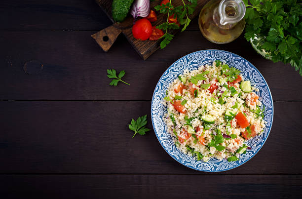 Traditional Lebanese Salad Tabbouleh. Couscous with parsley, tomato, cucumber, lemon and olive oil. Middle Eastern cuisine. Top view, copy space stock photo