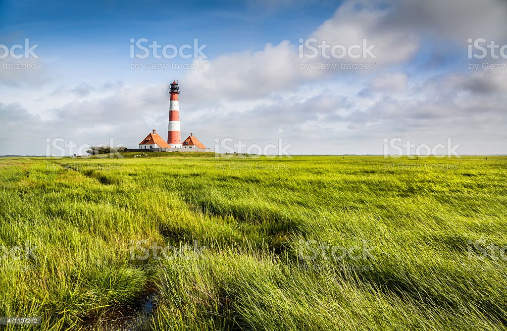 Traditional lighthouse at North Sea with blue sky and clouds stock photo