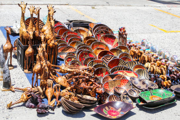 Traditional local african souvenir market on the street with rows of carved hand painted wooden bowls, giraffes, elephants with colorful tribal design in Hout Bay, South Africa Traditional local african souvenir market on the street with rows of carved hand painted wooden bowls, giraffes, elephants with colorful tribal design in Hout Bay, South Africa hout stock pictures, royalty-free photos & images