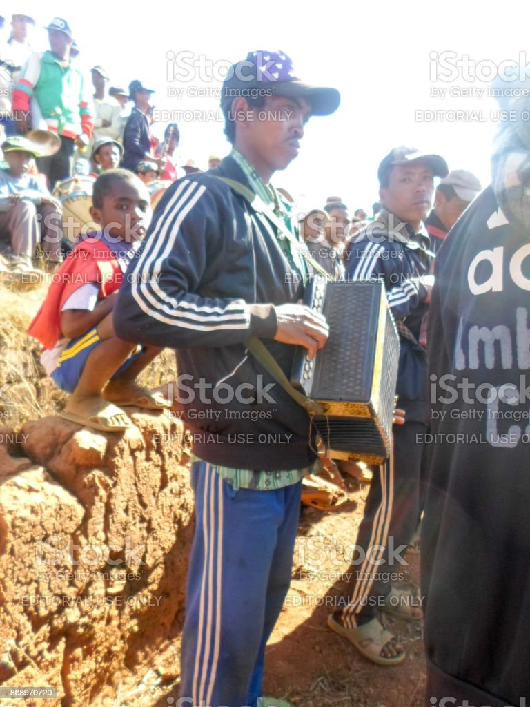 A traditional Malagasy musician posing with his accordion during the rite of 'famadihana' (exhumation) in the highlands stock photo