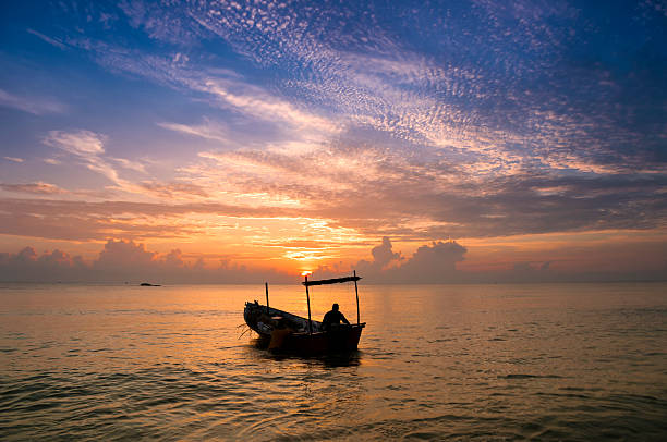 Traditional Malaysian fisherman at dusk stock photo