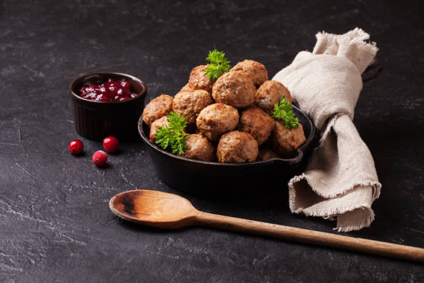 Traditional meatballs with cranberry sauce in a cast iron skillet Traditional meatballs with cranberry sauce in a cast iron skillet meatball stock pictures, royalty-free photos & images