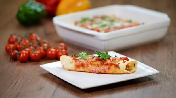 traditionelle mexikanische enchiladas mit hühnerfleisch, würziger tomatensauce und käse auf einem teller. mexikanische küche. - meeresfrüchte enchiladas stock-fotos und bilder