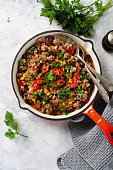 Traditional Mexican food - Chili con carne with minced meat and vegetables stew in tomato sauce in a cast iron pan on light gray slate or concrete background. Top view with copy space.