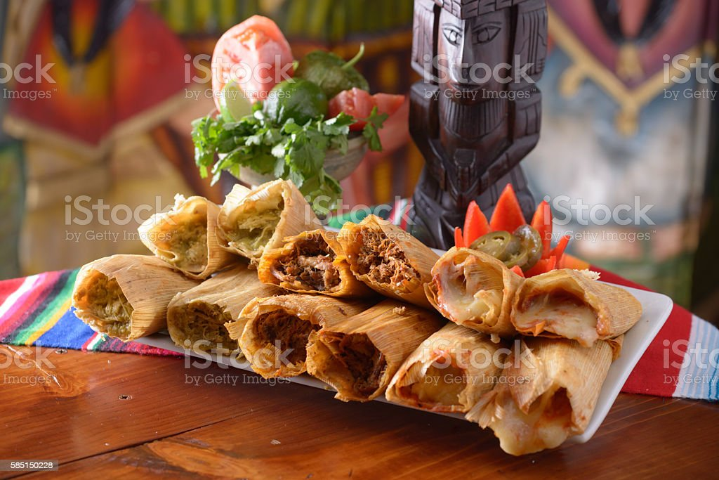 Traditional Mexican food tamales platter with garnishes stock photo