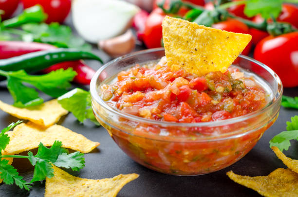 Traditional mexican homemade salsa sauce with ingredients, tomat Traditional mexican homemade salsa sauce with ingredients, tomatoes, pepper, cilantro, chips on a dark black stone table. Close-up, horizontal image salsa sauce stock pictures, royalty-free photos & images