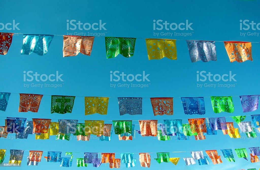 Traditional mexican paper bunting decoration celebratory flags against blue sky - foto de acervo