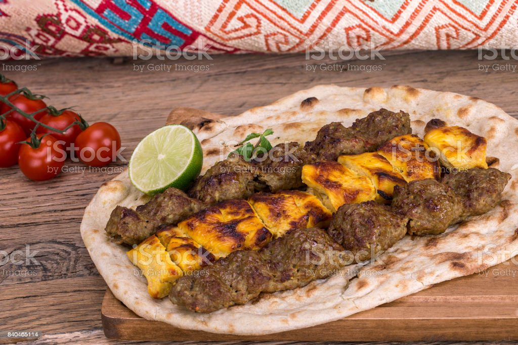 Traditional Middle eastern Persian chicken and lamb meat Shashlik Kebab (skewered meat) BBQ Grill on flat pita bread and saffron rice and tahchin and pomegranate on a dark background. Iranian cuisine stock photo