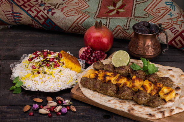 traditionelle nahöstliche persische huhn und lamm fleisch schaschlik kebab (fleisch aufgespießt) bbq grill auf flache pita-brot und safran-reis und tahchin und granatapfel auf einem dunklen hintergrund. persische küche - iranische stock-fotos und bilder