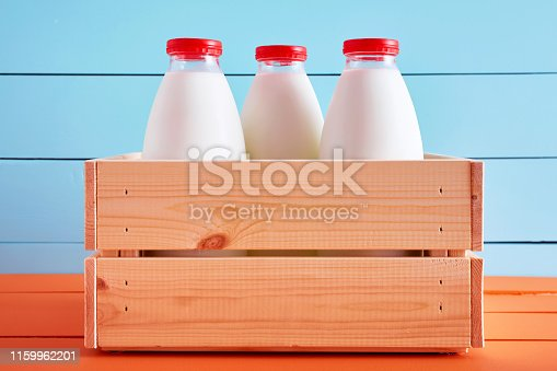 Milk bottles in a wooden crate on wooden kitchen table with blue wooden background.