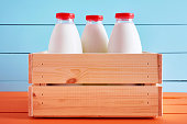 istock Traditional milk bottles in a wooden crate on wooden kitchen table with blue wooden background. 1159962201