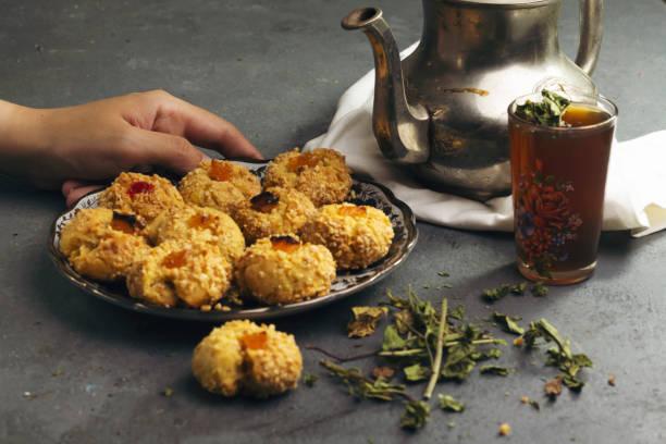 Traditioneller marokkanischer Tee mit orientalischen algerischen süßen Keksen ( mchawak   arabisch benannt, Teetasse und Topf und Minzblätter – Foto