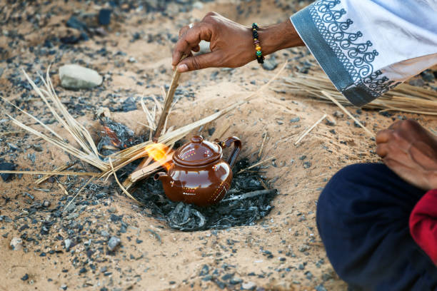 Traditional moroccan teapot in fire. Tea preparation in the desert. stock photo