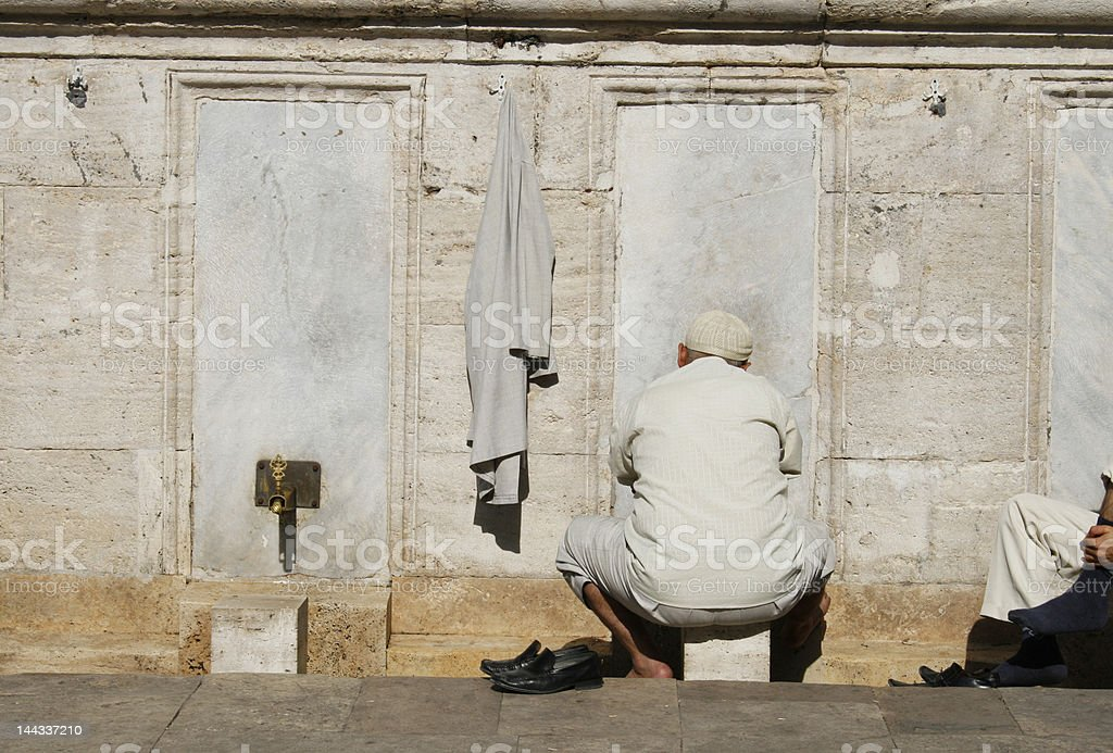 Traditional Muslim man washing feet in front of mosque royalty-free stock photo